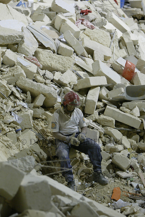 An exhausted Civil Protection officer sits on the rubble and starts removing his gloves after the lifeless bodies of two women, one Maltese and one Russian, were found and taken away, on the site where an apartment block collapsed, leaving a Maltese and a Russian woman dead, in the village of St Paul's Bay in the north of Malta early June 4, 2004.   The building collapsed because of excavation works taking place on a site adjacent to it. ..MALTA OUT..REUTERS/Darrin Zammit Lupi