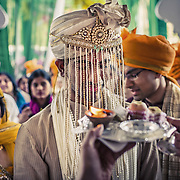 As he arrives at the wedding venue, the bride's mother greets the groom with a welcoming ritual. Udaipur, 2013