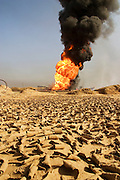 One of the oil wells set ablaze by retreating Iraqi troops in the southern Rumaila oil field. The wells were set on fire with explosives placed by retreating Iraqi troops when the US and UK invasion began. Seven or eight wells were set ablaze but at least one other was detonated but did not ignite. The Rumaila field is one of Iraq's biggest oil fields with five billion barrels in reserve. Many of the wells are 10,000 feet deep and produce huge volumes of oil and gas under tremendous pressure, which makes capping them very difficult and dangerous. Rumaila is also spelled Rumeilah.