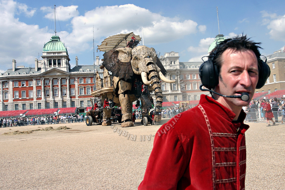 The gigantic mechanical elephant walking through his arena in central London, on Friday, May 5, 2006, while a member of the Royal De Luxe talk on his radiophone. The Sultan's Elephant show, for the first time in London is a magical, and unique in the world, theatrical show across the streets, performed by an international French company - Royal De Luxe - specialised in constructing and giving 'life' to enormous mechanical puppets. The Sultan's Elephant is the story of a Sultan dreaming of a little girl that travels through time. **ITALY OUT**