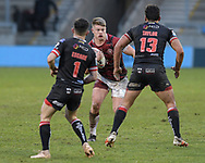 Morgan Smithies (15) of Wigan Warriors looks for a way past Morgan Escare (1) and Elijah Taylor (13) of Salford Red Devils