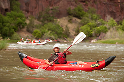 North America, United States, Colorado, Dinosaur National Monument, Green River (Gates of Lodore section), boy in kayak.  MR
