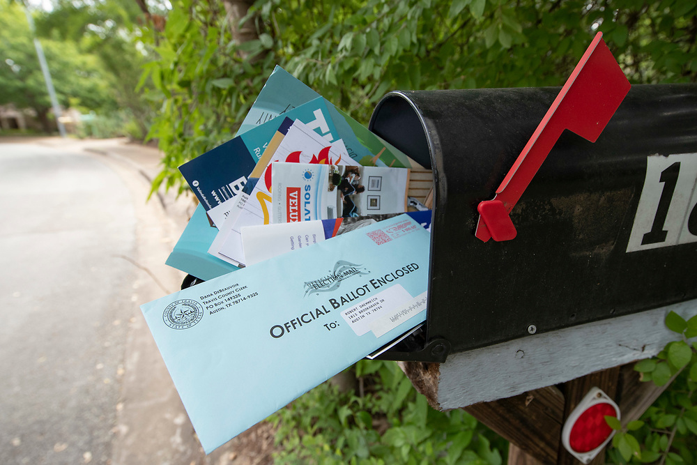 Austin, TX USA July 6, 2020:  A 65-year old Texan receives a mail-in ballot from the Travis County Clerk's office for a July runoff election that will determine November main election matchups. Accusations of voter fraud regarding mail in ballots continue to swirl in Texas even though no evidence supports any widespread fraud.