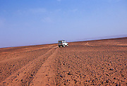 White Land Rover crossing the stony desert floor leaving a dust trail behind in the Sahara Desert, Morocco