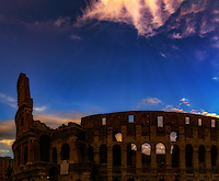 """""""The mystical twilight descends on the Colosseum in Rome""""…<br /> <br /> This image was created combining two images into a panorama of the ancient Colosseum at twilight.  The Colosseum, is an elliptical amphitheatre in the center of the city of Rome, the largest ever built during the Roman Empire. One of the greatest works of Roman architecture and engineering in history, its construction started in 72 AD under the emperor Vespasian and was completed in 80 AD under Titus. Capable of seating 65,000 spectators, it was used for gladiatorial contests and public spectacles. The building ceased to be used for entertainment in the early medieval era. It is one of Rome's most popular tourist attractions and still has close connections with the Roman Catholic Church, as each Good Friday the Pope leads a torch lit """"Way of the Cross"""" procession that starts in the area around the Colosseum.  The Colosseum is generally regarded by Christians as a site of the martyrdom of large numbers of believers during the persecution of Christians in the Roman Empire, as evidenced by Church history and tradition.  A Cross stands exultant in the Colosseum center with a plaque stating:  """"The amphitheatre, one consecrated to triumphs, entertainments, and the impious worship of pagan gods, is now dedicated to the sufferings of the martyrs purified from impious superstitions.""""  In viewing many historical sites during my journey in Italy, seeing the iconic Colosseum for the first time…I became awestruck.   It is as grand in person as it appears in the media, and it seems to hold a very mystical aura.  Climbing the ancient steps inside, one cannot help but feel not only the suffering of its past, but the forgiveness and sacrifice of its present stature.  As evening descended on the ancient Colosseum, the sun and the clouds performed a mystical light show to the delight of the weary travelers and one adrenalized photographer."""