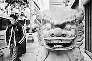 A man walks past a statue of a dragon at the entrance to Chinatown in San Francisco.