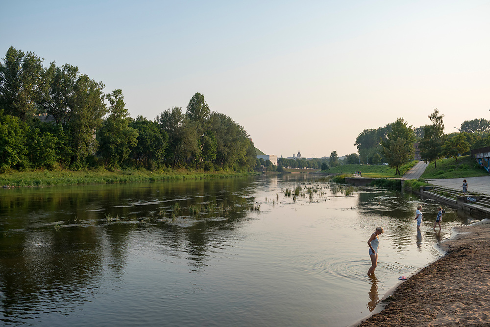 Vilnius, Lithuania - August 11, 2015: People stand in the shallows of the Neris River late on a summer day in Vilnius, Lithuania. The Neris, which originates in Belarus, flows through the city of Vilnius.