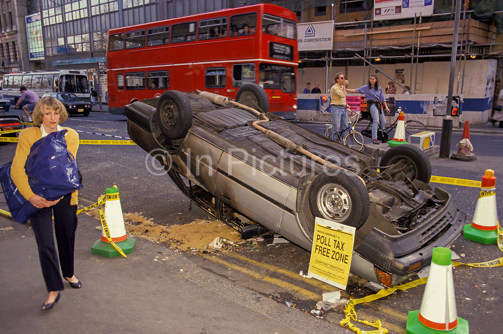 A pedestrian walks past an upturned car, a casualty of the Poll Tax riot, on 1st April 1990, in Charing Cross Road, London, England. when angry crowds, demonstrating against Margaret Thatchers local authority tax, stormed the Whitehall area and then Londons West End, setting fire to a construction site and cars, looting stores up Charing Cross Road and St Martins Lane, on 1st April 1990, in London, England. The anti-poll tax rally in central London erupted into the worst riots seen in the city for a century. Forty-five police officers were among the 113 people injured as well as 20 police horses. 340 people were arrested.