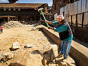 03 MARCH 2017 - BHAKTAPUR, NEPAL: A man uses a sledge hammer to break rocks that will be used in reconstruction of Bhaktapur's Durbur Square, the historic center of the city. Bhaktapur, a popular tourist destination and one of the most historic cities in Nepal was one of the hardest hit cities in the earthquake. Recovery seems to have barely begun nearly two years after the earthquake of 25 April 2015 that devastated Nepal. In some villages in the Kathmandu valley workers are working by hand to remove ruble and dig out destroyed buildings. About 9,000 people were killed and another 22,000 injured by the earthquake. The epicenter of the earthquake was east of the Gorka district.      PHOTO BY JACK KURTZ