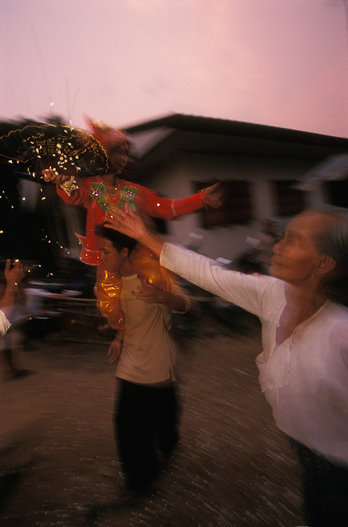 An old woman throws rice at one of her great grandsons while he dances on the shoulders of a relative during Poy Sang Long, the yearly ordination of novice monks, Mae Hong Son, Thailand.