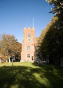 Trees in autumn leaf in churchyard of St Thomas church, Bradwell on Sea, Essex, England