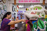 31 JANUARY 2014 - BANGKOK, THAILAND:   The owner of a clock shop tips a Lion dance troupe that performed in her shop during Lunar New Year festivities, also know as Tet and Chinese New Year, in Bangkok. This year is the Year of the Horse. The Lion Dance scares away evil spirits and brings prosperity and luck. Ethnic Chinese make up about 14% of Thailand and Chinese holidays are widely celebrated in Thailand.     PHOTO BY JACK KURTZ