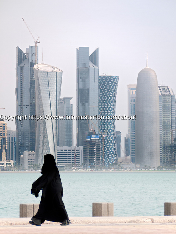 Women walking on The Corniche with modern office towers and skyline in business district in Doha Qatar