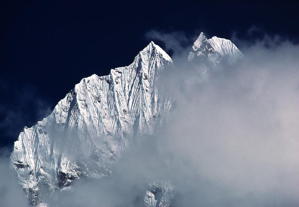 Tamserku Peak rises above the mists in the Khumbu Himalaya in Sagarmatha, or Everest, National Park in Nepal.