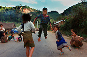 A Laos highway road is the only flat surface for Hmong children living on a steep slope to jump their string of rubber bands tied together in December 2000.  Few Hmong make it past the third grade. Some villages still don't have schools. Parents often put their daughters to work instead of sending them to school.