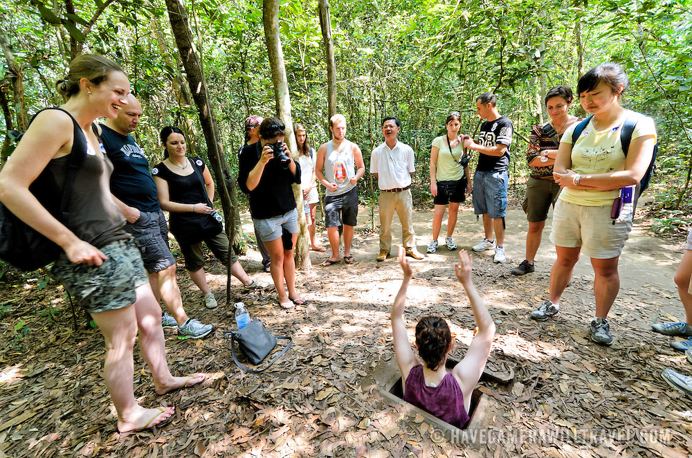 Tourists try to slip down into one of the many camouflaged entrances to the tunnel complex. The Cu Chi tunnels, northwest of Ho Chi Minh City, were part of a much larger underground tunnel network used by the Viet Cong in the Vietnam War. Part of the original tunnel system has been preserved as a tourist attraction where visitors can go down into the narrow tunnels and see exhibits on the defense precautions and daily life of the Vietnamese who lived and fought there.