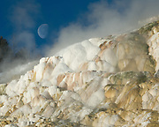 The moon sets over Canary Spring in Yellowstone National Park.