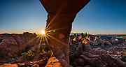 Sunrise sunburst on the red-orange sandstone of Skyline Arch at Devils Garden Campground, Arches National Park, Moab, Utah, USA. This image was stitched from multiple overlapping photos. A thick underground salt bed underlies the creation of the park's many arches, spires, balanced rocks, sandstone fins, and eroded monoliths. Some 300 million years ago, a sea flowed into the area and eventually evaporated to create the salt bed up to thousands of feet thick. Over millions of years, the salt bed was covered with debris eroded from the Uncompahgre Uplift to the northeast. During the Early Jurassic (about 210 million years ago) desert conditions deposited the vast Navajo Sandstone. On top of that, about 140 million years ago, the Entrada Sandstone was deposited from stream and windblown sediments. Later, over 5000 feet (1500 m) of younger sediments were deposited and then mostly worn away, leaving the park's arches eroded mostly within the Entrada formation.