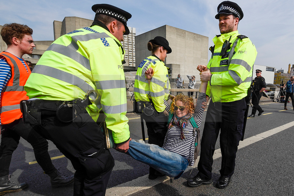 """© Licensed to London News Pictures. 18/04/2019. LONDON, UK.  Police arrest a protester on Waterloo Bridge during """"London: International Rebellion"""", on day four of a protest organised by Extinction Rebellion.  Protesters are demanding that governments take action against climate change.  Marble Arch, Oxford Circus, Piccadilly Circus, Waterloo Bridge and Parliament Square have been blocked by activists in the last three days.  Police have issued a section 14 order requiring protesters to convene at Marble Arch only so that the protest can continue.  Photo credit: Stephen Chung/LNP"""