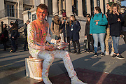 Braydon, a performer allowing himself to be squirted with paint while sitting on a toilet he found on a skip by tourists outside the National Gallery, Trying to earn enough money to buy some chairs for a pop up cafe he wants to open. Trafalgar sq. London. 17 March