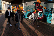 With local coronavirus lockdown measures in place and Birmingham currently set at 'Tier 2' or 'high', people wearing face masks pass street art on boarded up shops which are closed in city centre on 26th October 2020 in Birmingham, United Kingdom. The three tier system in the UK has levels: 'medium', which includes the rule of six, 'high', which will cover most areas under current restrictions; and 'very high' for those areas with particularly high case numbers. Meanwhile there have been calls by politicians for a 'circuit breaker' complete lockdown to be announced to help the growing spread of the Covid-19 virus.