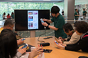 Elderly people learning how to use the iphone interface to control applications and use chat forums and payments. Applestore, Shanghai, China