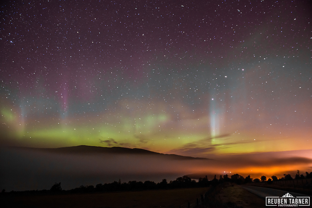 The Aurora Borealis (Northern Lights) light up the sky above Inverness in the Highlands of Scotland as a cloud inversion settles over Loch Ness.