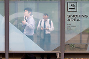 Japanese salarymen or male office workers enjoy cigarettes in a smoking area in Chuo Park, Shinjuku, Tokyo, Japan. Friday March 22nd 2019