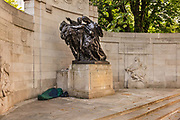 Man sleeping rough on the Thames Embankment under the Monument commemorating WWI during the coronavirus pandemic on the 10th May 2020 in London, United Kingdom. The Anglo-Belgian Memorial, also known as the Belgian Gratitude Memorial or the Belgian Refugees Memorial, is a war memorial on Victoria Embankment in London, opposite Cleopatras Needle. It was a gift from Belgium, as a mark of thanks for assistance given by the UK during the First World War, and in particular for sheltering thousands of Belgian refugees who fled from the war.