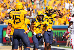 Sep 14, 2019; Morgantown, WV, USA; West Virginia Mountaineers running back Leddie Brown (4) celebrates with teammates after scoring a touchdown during the fourth quarter against the North Carolina State Wolfpack at Mountaineer Field at Milan Puskar Stadium. Mandatory Credit: Ben Queen-USA TODAY Sports