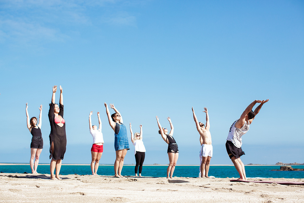 People enjoying a healthy lifestyle of yoga exercise on the beach at the Minquiers, surrounded by turquoise, calm water and sunshine in Jersey, CI