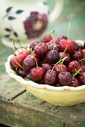 Cherries in cream ceramic bowl