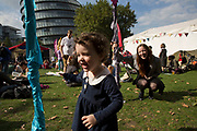 People gathering to hang out, listen to bands and other activities at the Blue Ribbon Village. A woman plays with her god-daughter amongst the silks flags. Totally Thames takes place over the whole month in September, combining arts, cultural and river events presented by Thames Festival Trust throughout the 42-mile stretch of the River Thames in London, UK.