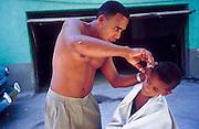 25 JULY 2002 - HAVANA, HAVANA, CUBA: A man cuts his son's hair in front of their apartment in Havana, Cuba, July 25, 2002..PHOTO BY JACK KURTZ