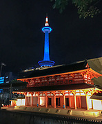Nightime view of the Kyoto Tower and a miniature shrine model in the foreground