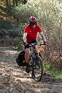 Mountain bike rider (Reuben) cycling through soft sand in a pleasant woodland bridleway near Bridgend, Wales