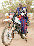 Maasai tribesman sitting on motorcycle, near Amboseli National Park, Rift Valley Province, Kenya