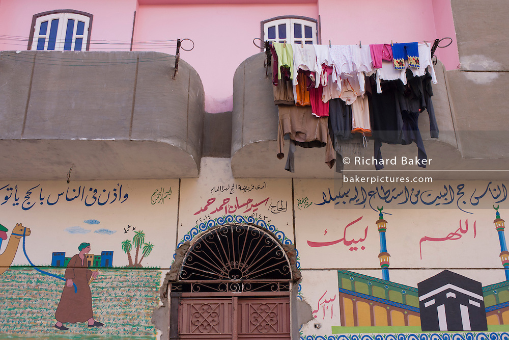 Washing dries from a balcony above an Islamic wall mural in Gezirat, a village on the West Bank of Luxor, Nile Valley, Egypt.