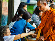 """17 MARCH 2018 - BANGKOK, THAILAND:  Buddhist monks collect alms from the crowd during a """"sticky rice merit making"""" in Lumpini Park in Bangkok. Sticky rice merit making is a merit making in the Isan / Lao style, when people present small amounts of cooked sticky rice (also known as glutinous rice) to Buddhist monks. Isan is the northeast region of Thailand.    PHOTO BY JACK KURTZ"""