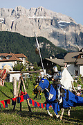 Beneath the Sella Group in the Dolomites, a knight in shining armor rides a horse in a medieval festival, in Selva di Val Gardena, Italy. The beautiful ski resort of Selva di Val Gardena (German: Wolkenstein in Gröden; Ladin: Sëlva Gherdëine) makes a great hiking base in the Trentino-Alto Adige/Südtirol (South Tyrol) region of Italy, in the Dolomites, part of the Southern Limestone Alps, Europe. UNESCO honored the Dolomites as a natural World Heritage Site in 2009.