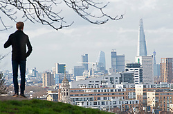 © Licensed to London News Pictures. 12/02/2019. Greenwich, A young man enjoing the view over London from Greenwich Park. Bright and milder weather today in Greenwich Park, South East London . Photo credit: Grant Falvey/LNP
