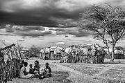 Women in a  Samburu village beneath a storm cloud sky, black and white ,Samburu, Kenya, Africa