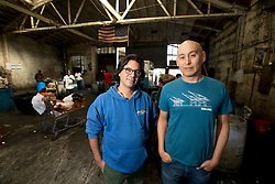 """Amir Soltani, left, and Chihiro Wimbush pose for a photograph at the Alliance Recycling center in west Oakland, Calif., Tuesday, Oct. 6, 2015. The pair of documentary filmmakers made Alliance the subject of """"Dogtown Redemption,"""" which premieres at the Mill Valley Film Festival on Thursday, Oct. 15. (D. Ross Cameron/Bay Area News Group)"""