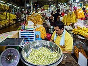 27 FEBRUARY 2019 - BANGKOK, THAILAND:  A vender in Pak Klong Talat, Bangkok's famous flower market. Bangkok, a city of about 14 million, is famous for its raucous nightlife. But Bangkok's real nightlife is seen in its markets and street stalls, many of which are open through the night.         PHOTO BY JACK KURTZ