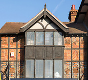 Facade of historic 1925 building heraldic symbols and signs, 105 High Street, Marlborough, Wiltshire, England, UK