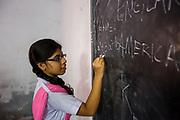 A schoolgirl writing a mathematical formula on a blackboard in a classroom, Sursuna High School, Sursana, Kolkata, India