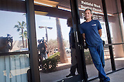 """Sept. 6, 2009 -- TEMPE, AZ: TIM FARWELL, the security guard for the strip mall that houses the Faithful Word Baptist Church, guards the church in Tempe, AZ, Sunday. Steven Anderson, the minister at the Faithful Word Baptist Church, an independent fundamentalist Baptist church, in Tempe has repeatedly said he hoped US President Barack Obama would die from a brain tumor and Sunday, Sept. 6, reiterated that he """"hates"""" President Obama. More than 200 people from a variety of liberal and progressive churches in the Phoenix area picketed Anderson's church Sunday morning, outnumbering his small congregation of about 50.  Photo by Jack Kurtz"""
