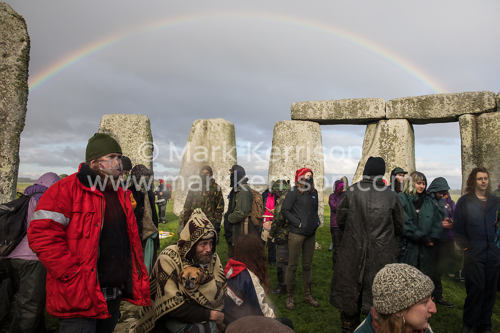 Salisbury, UK. 5th December, 2020. A rainbow appears behind over one hundred people, including local residents, climate and land justice activists and pagans, taking part in a Mass Trespass at Stonehenge. The trespass was organised in protest against the approval by Transport Secretary Grant Shapps of a £1.7bn project for a two-mile tunnel beneath the World Heritage Site and a further eight miles of dual carriageway for the A303, as well as the government's £27bn Road Investment Strategy 2 (RIS2).