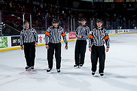 KELOWNA, BC - FEBRUARY 15: Referees Brayden Arcand and Matt Hicketts, and linesmen Dustin Minty and Jade Portwood, exit the ice after the win for the Red Deer Rebels at the against the Kelowna Rockets at Prospera Place on February 15, 2020 in Kelowna, Canada. (Photo by Marissa Baecker/Shoot the Breeze)