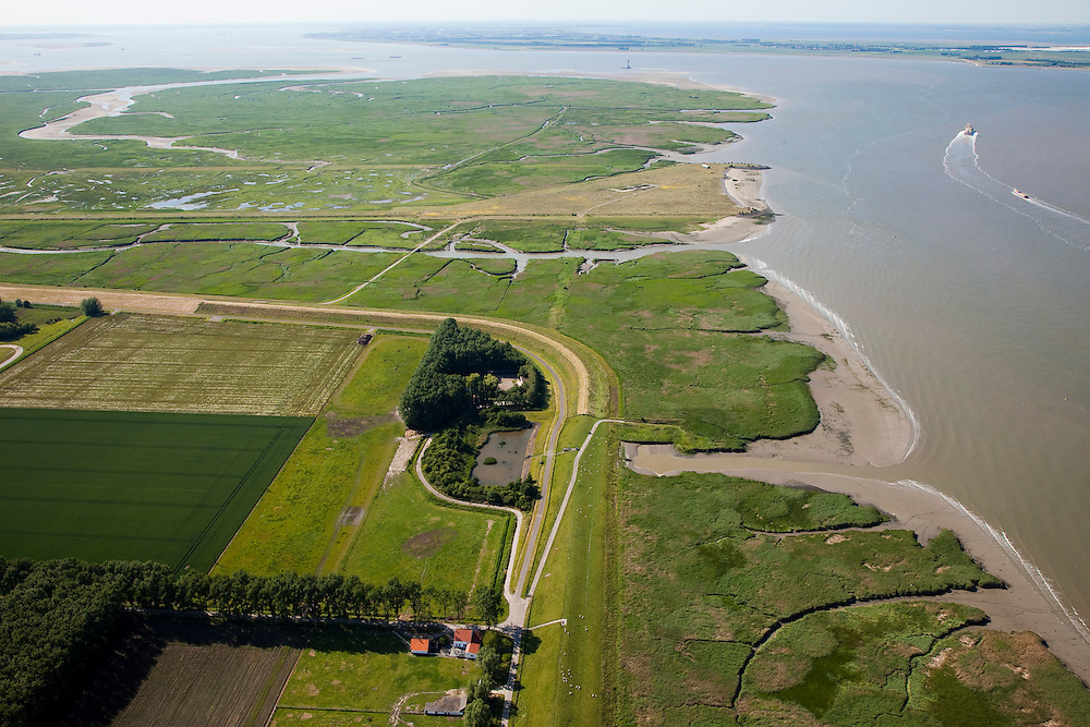 Nederland, Zeeland, Zeeuws-Vlaanderen, 12-06-2009; Hertogin Hedwigepolder met Verdronken Land van Saeftinghe in de achtergrond, het Nauw van Bath midden aan de horizon. In verband met de komende verdieping van de vaargeul van de nabijgelegen Westerschelde, moet er volgens de Europese habitatrichtlijn natuurcompensatie komen. Door deze polder en de nabijgelegen Belgische Prosperpolder, a te ontpolderen, wordt er grond terug gegeven aan de natuur, zogenaamde natuurcompensatie (advies commissie onder leiding van Ed Nijpels). De maatregelen zijn omstreden, in het Belgisch deel van het gebied is men echter reeds begonnen..Hertogin Hedwigepolder with Drowned Land of Saeftinghe in the background. Because of the future enlargement of the fairway of the nearby Westerschelde, the nature has to be compensated (according to the European Habitats Directive). The Hertogin Hedwige polder (and the adjacent Belgian polder - on the other side of the border - the Prosperpolder) are to be given back to nature, i.e. are to be 'de-polderd'. The measures are controversial, but in the Belgian part of the polders works have already been started.Swart collectie, luchtfoto (25 procent toeslag); Swart Collection, aerial photo (additional fee required).foto Siebe Swart / photo Siebe Swart